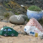 A collection of rocks painted to look like village buildings, overlooking the sea.