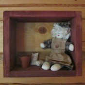 Fabric doll in shadow box.