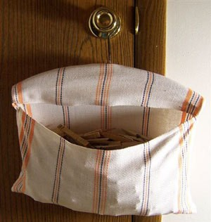 Tea towel on wooden hanger clothespin bag.