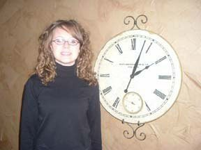 Teen girl next to clock.