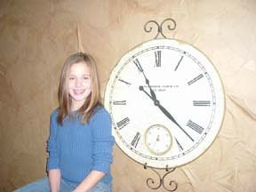 Girl next to clock.