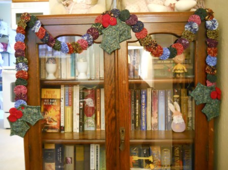 Garland hanging draped on antique wooden bookcase.