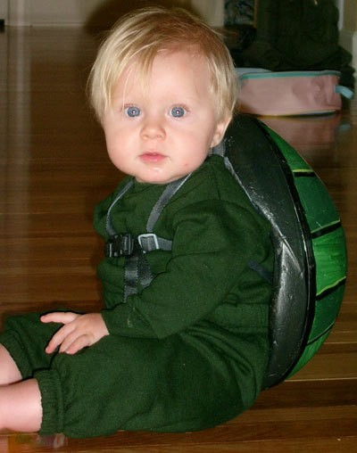 Frontal view of baby with helmet strapped on his back.