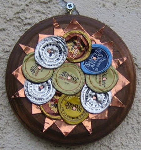 A sun ornament made from bottle caps.