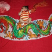 Baby lying on red background with dragon banner.