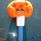 A mini pumpkin on a flashlight.