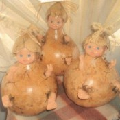 Gourds with baby dolls inside simulating a baby popping out of the gourd.