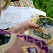 A woman doing cross stitch.