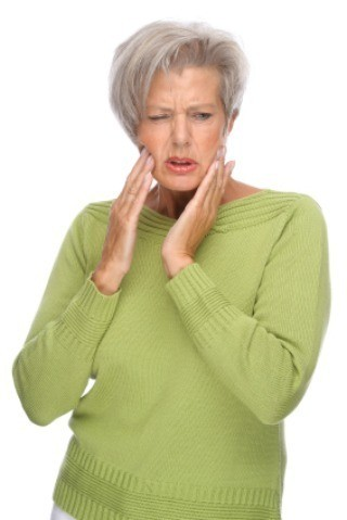 A woman in pain wearing dentures.
