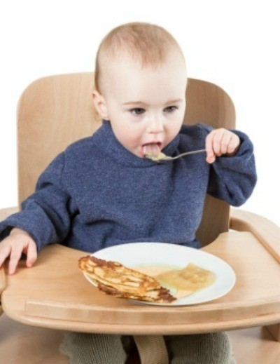 Eating pancakes with applesauce.