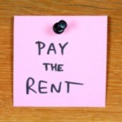 Sticky note reminder to pay the rent.