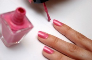 A woman putting on nail polish.