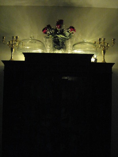 Lights on top of cabinet, reflecting off wall.