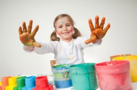 A kid finger painting.