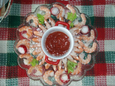 A plate of shrimp appetizers around cocktail sauce