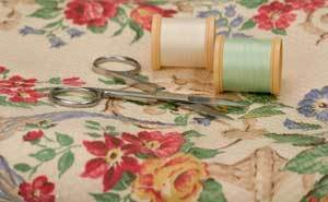 Flowered sheet, spools of thread, and scissors.