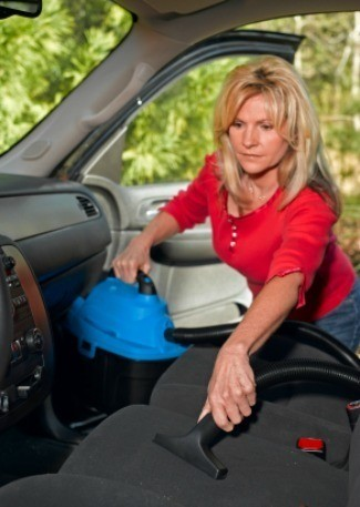 A woman cleaning out the interior of her car.