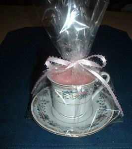 Cup and saucer candle wrapped in clear paper and tied with a pink bow.