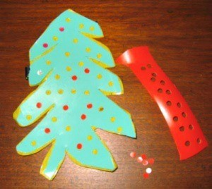 tree shape cut from a green laundry soap bottle with ornaments punched from a red one
