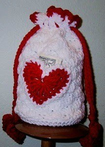 white crochet purse with red heart and pull strings