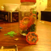 Side view of jar with toys inside and next to it on table.