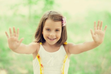 a young girl holding up both hands