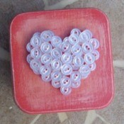 Pink box with white buttons arranged in the shape of a heart.