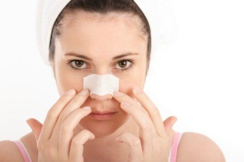 A woman with a pore strip on her nose.