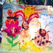 Cardboard drawing of flower, sun, bunny, and ladybug with holes for faces.
