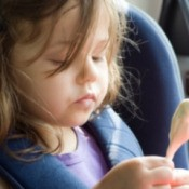 A child eating ice cream in a car.