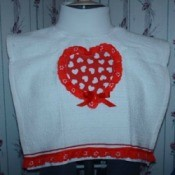 Tea towel cut for bib and decorated with Valentine's Day motif.