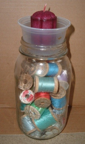 Candle holder on top of jar filled with spools of thread.
