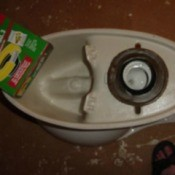 View of the underside of a toilet, including wax ring.