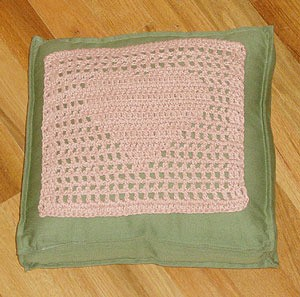 Pink filet crochet heart square on green pillow.
