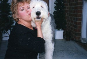 Woman kissing sheepdog