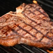 A T-bone steak on a grill.