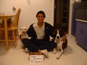 Teen sitting with Scruffy and another dog, with Happy Birthday sign on floor.