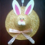 Straw hat with bunny ears, face, and a bow.
