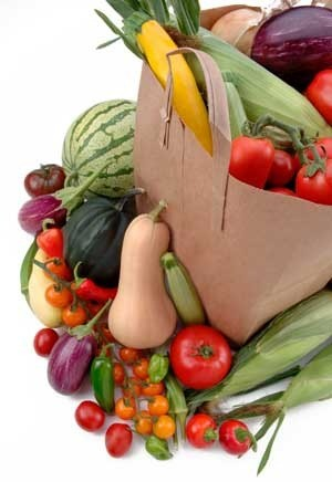 Bag filled with and surrounded by veggies.