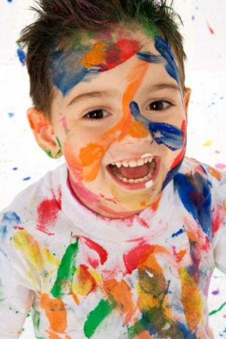 A kid with paint all over his face and clothes.