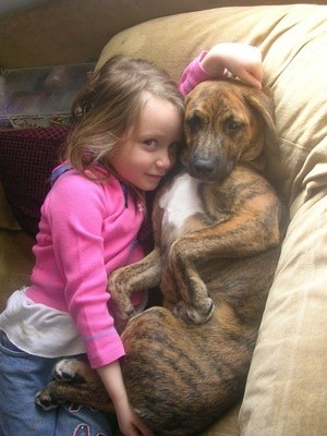 Sasha on couch with young girl.