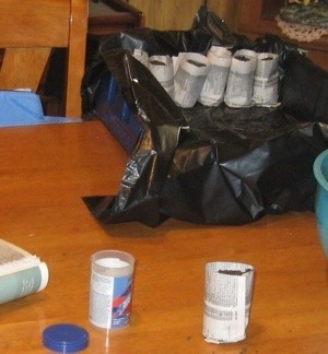 Gardening: Paper Pots - making the pots with completed ones in a plastic bag lined container in the background, closeup