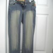 Pair of faded blue jeans hanging in front of door