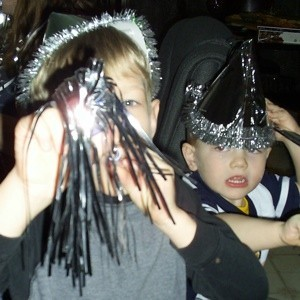 Two kids with hats and horns, celebrating New Year's Eve.
