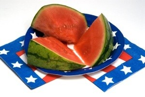 A watermelon on patriotic plates.
