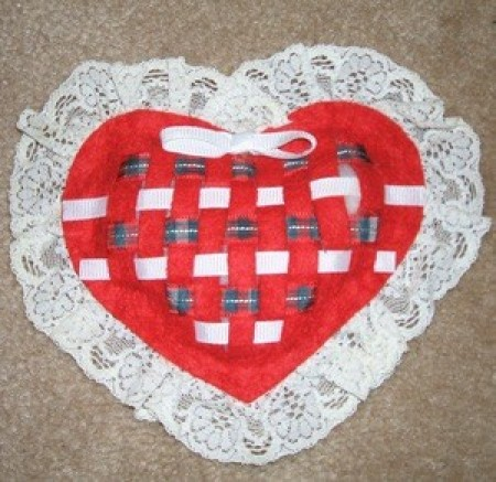 A woven felt sachet in the shape of a heart.