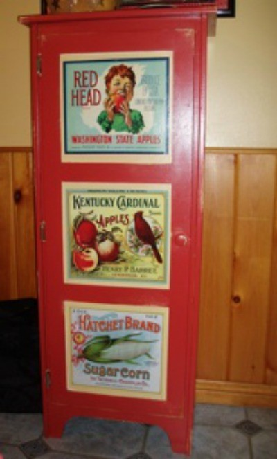 red painted cupboard with decoupaged calendar pages