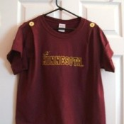 maroon t-shirt hanging on hanger on door