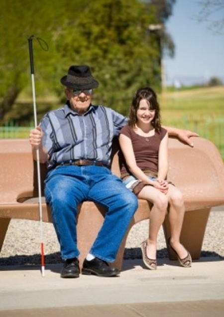 a blind man and a girl sitting on a bench