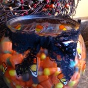 fish bowl filled with candy corn and tied with Halloween ribbon